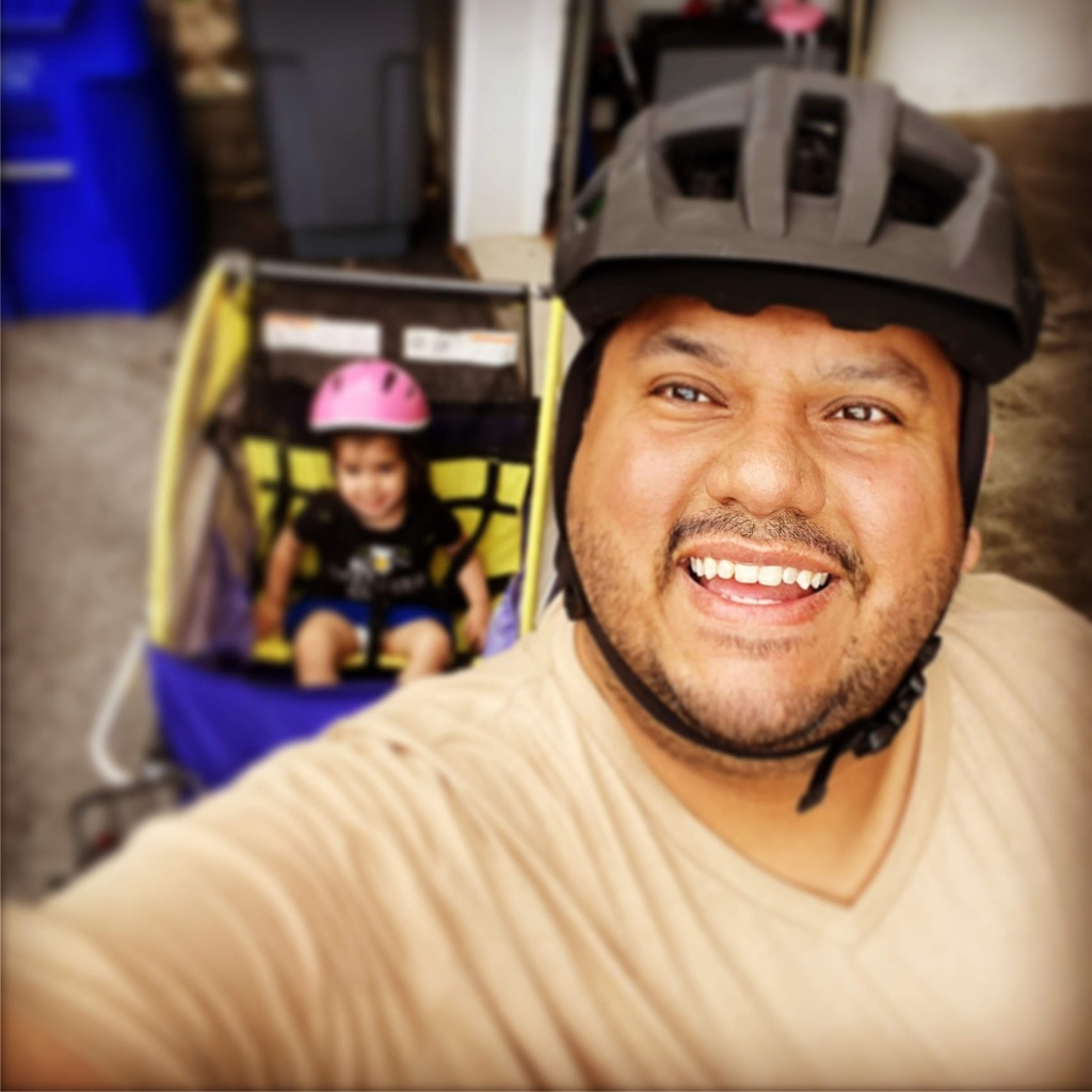 Image of a man wearing a bicycle helmet and smiling at the camera. Behind him is a little girl with her own pink bicycle helmet and smiling at the camera as well.