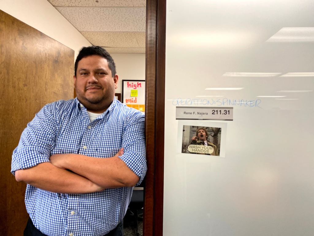 "Image of a man standing at the threshold to a door. He has his arms crossed and is smiling at the camera. He is wearing a blue shirt. The sign to his door reads ""Operation Spinnaker"" and ""Rene F Najera, 211.31"" and there is an image taped to the side of the door with a man pointing at the camera and a caption reading, ""Wash your hands!"""