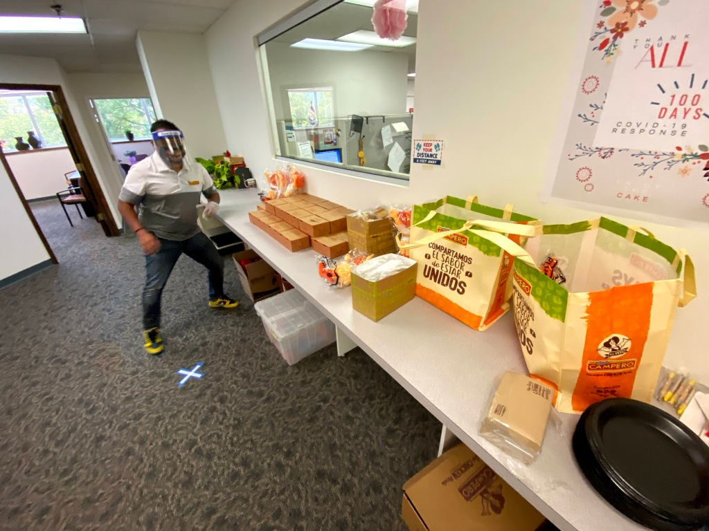 Image of a man standing in front of several boxes of food sitting on a table. He is wearing a face shield and a mask.