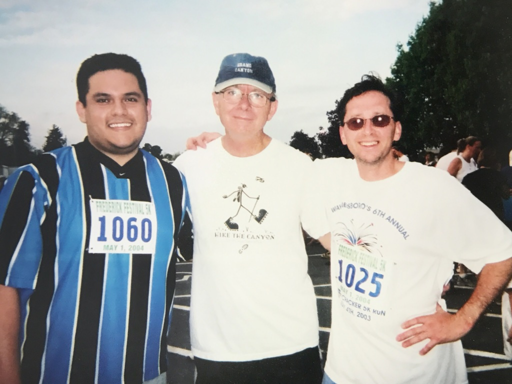 Image of three men standing together and smiling at the camera as they're wearing racing bibs and sports clothing.